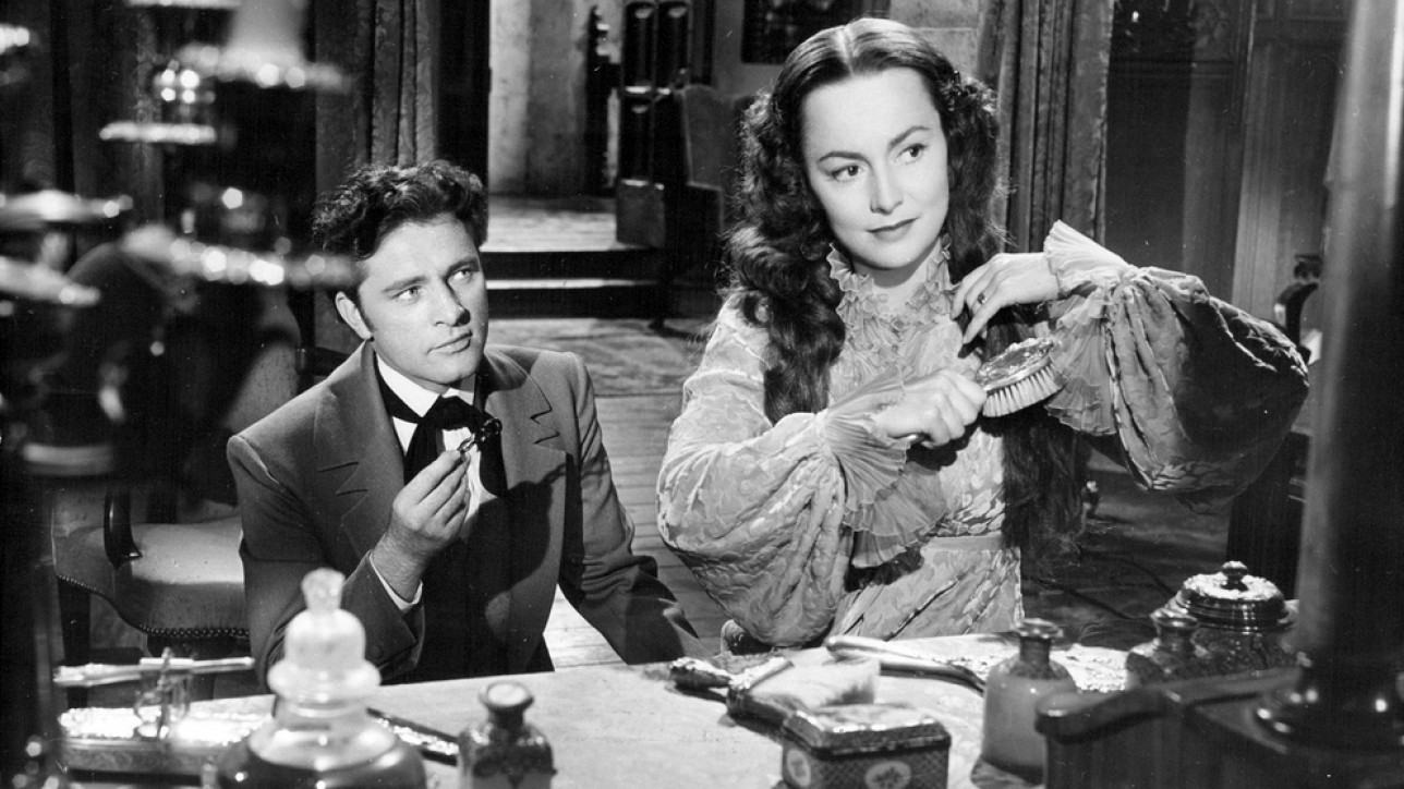 Olivia de Havilland and Richard Burton publicity photo in My Cousin Rachel, 1952. By Unknown - eBay, Public Domain.